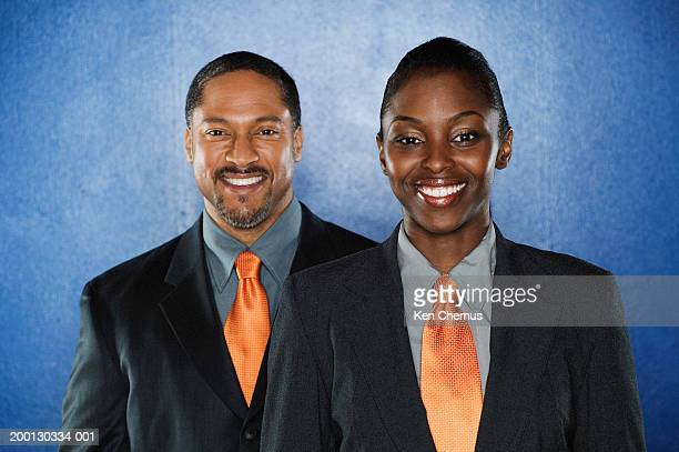Male and female business executives in matching suits, portrait