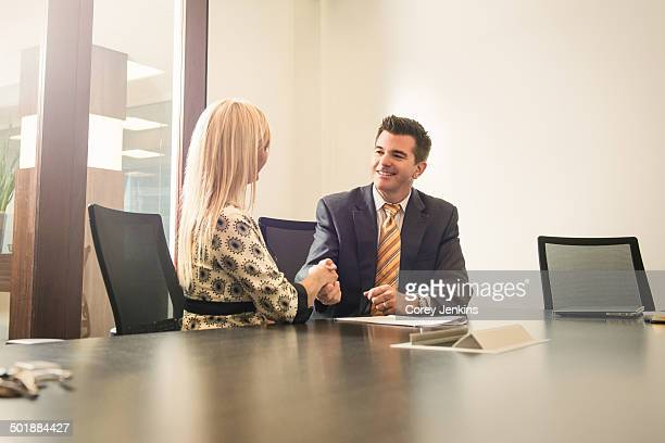 Male and female business lawyers shaking hands in office