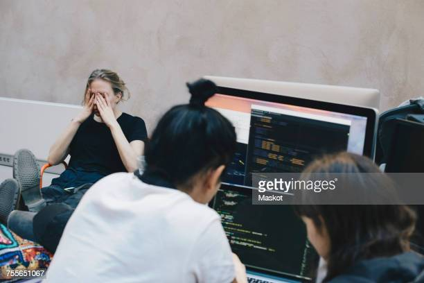 Male and female computer programmers using computer at office