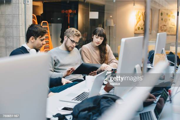 Male and female computer programmers using digital tablet at desk in office