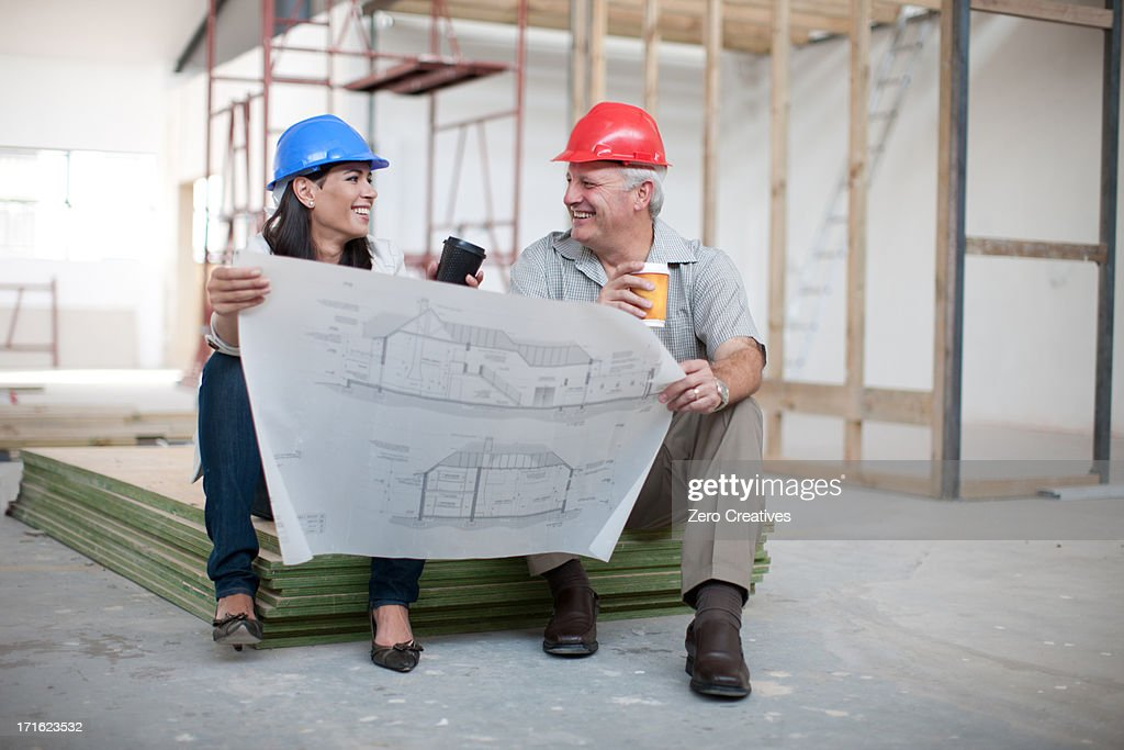Male and female construction workers sitting down holding coffee and male and female construction workers sitting down holding coffee and a blueprint stock photo malvernweather Choice Image