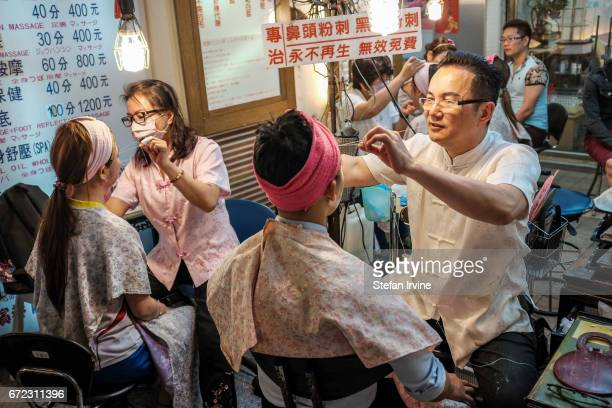 Male and female customers are having their eyebrows shaped using the traditional technique of threading right next to the Raohe Street Night Market...