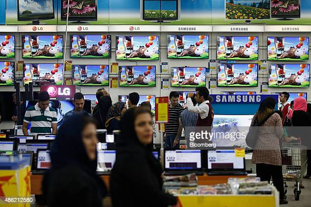 Male and female customers browse Samsung Electronics Co and LG Electronics Inc flat screen televisions displayed in an electronics store at the...