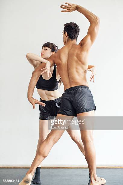 Male and female dancers dancing against wall