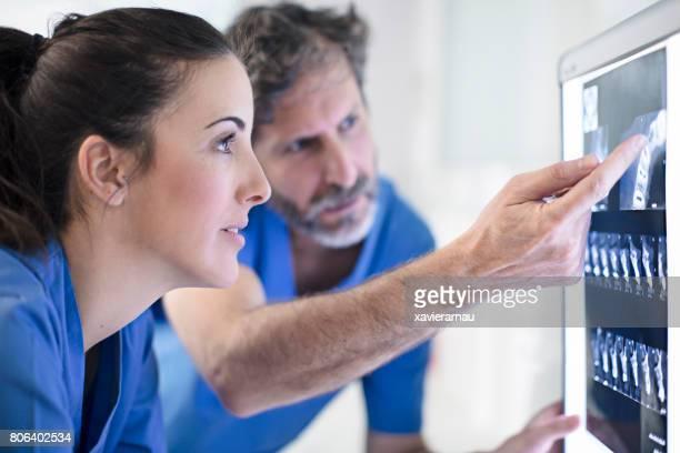 Männliche und weibliche Zahnärzte diskutieren Röntgenbild