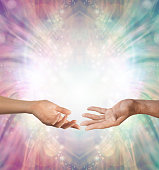 A female hand and a male hand with open palms facing each other against a beautiful intricate masculine and feminine colored energy background with copy space above