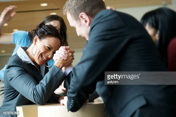 Male and female executive arm wrestling