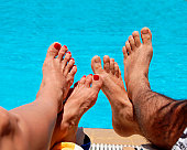 male and female feet by blue swimming pool