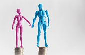 Male and female figurines holding hands looking at eachother, standing on top of equal piles of coins. Income equality concept with copy space