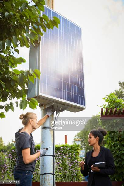 Male and female garden architects discussing by solar panel