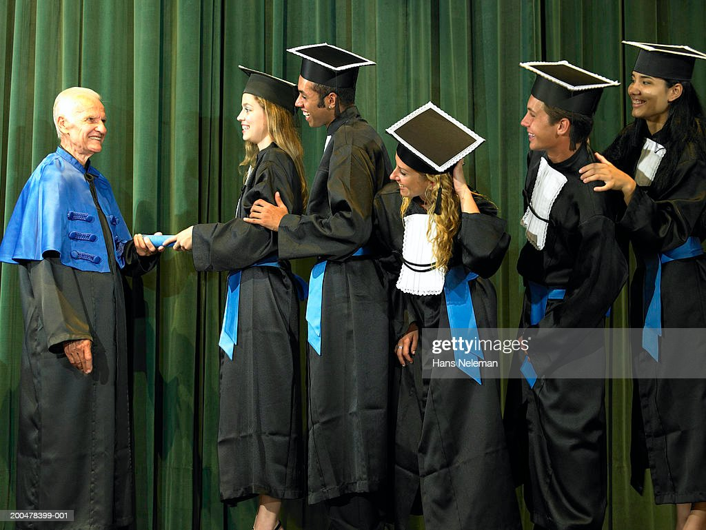 Male and female graduates in line receiving diplomas from dean : Stock Photo