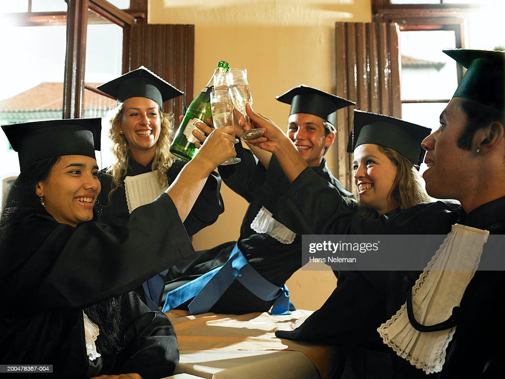 Male and female graduates toasting with champagne : Stock Photo