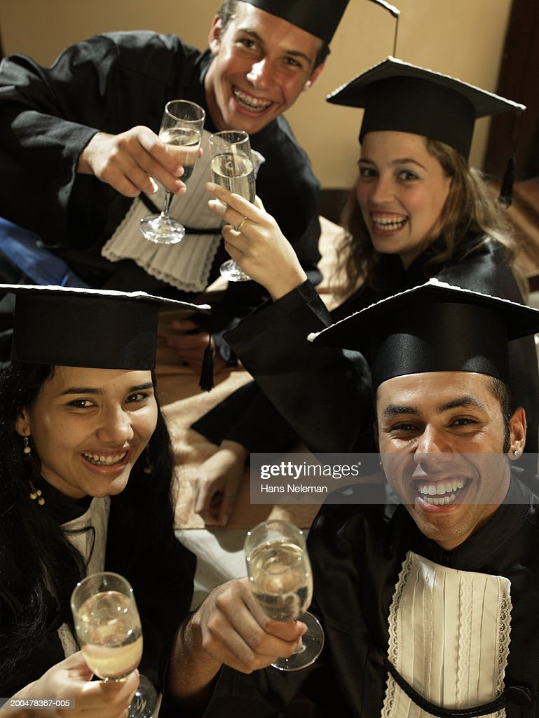 Male and female graduates toasting with champagne, portrait, elevated : Stock Photo