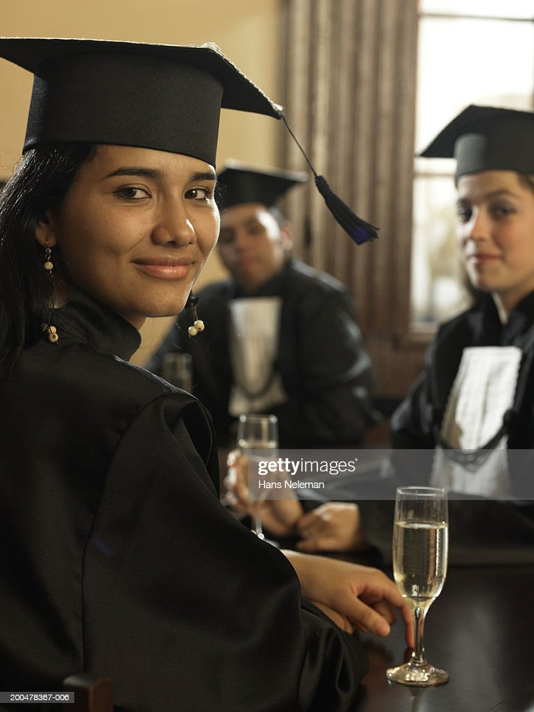 Male and female graduates with champagne, portrait : Stock Photo