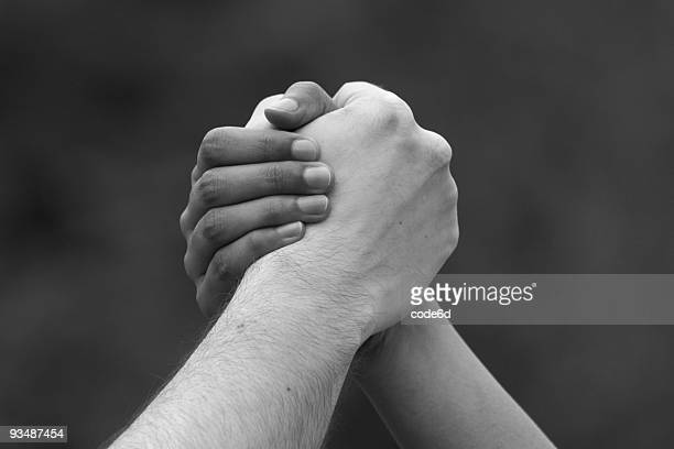 Male and female hands clasped, ethnicity concept, black & white