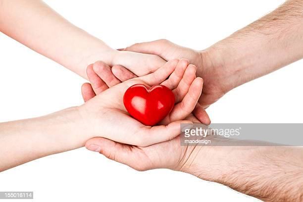 Male and Female Hands Holding Red Wooden Heart