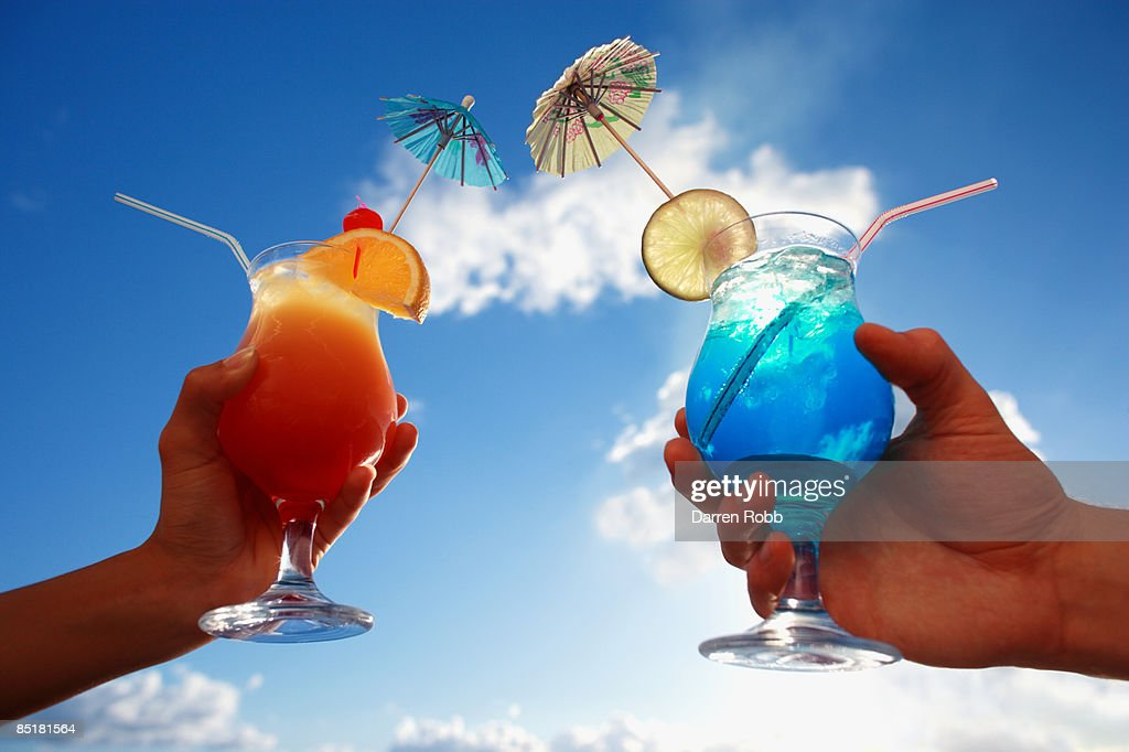 Male and female hands holding tropical cocktails