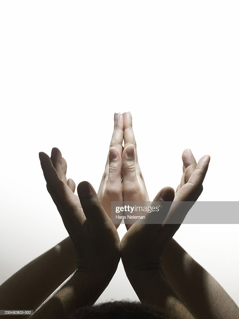 Male and female hands making worship and prayer signs, respectively : Stock Photo