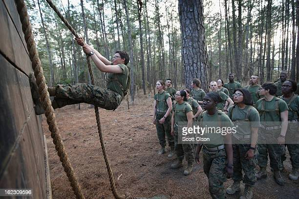 Male and female Marines wait to climb an obstacle on the Endurance Course during Marine Combat Training on February 20 2013 at Camp Lejeune North...