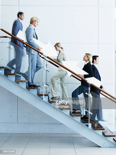 Male and female office workers on staircase holding arrow signs