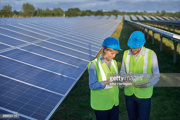 Male and female on solar farm looking at clipboard