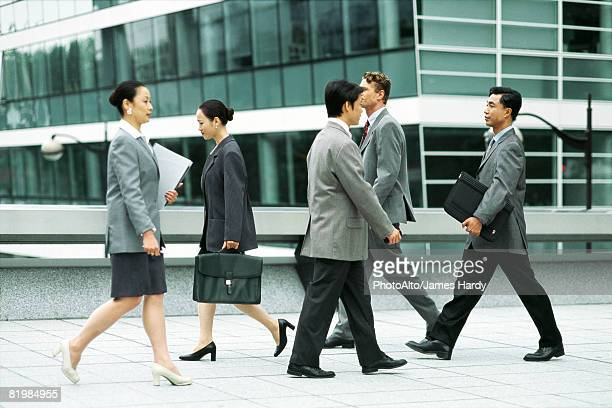 Male and female professionals walking on busy sidewalk, side view