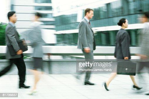 Male and female professionals walking on sidewalk, blurred motion
