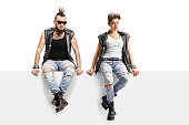 Male and female punkers sitting on a panel isolated on white background
