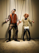Male and female puppets tied with string