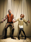 Male and female puppets tied with strings
