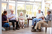 Male And Female Residents Sitting In Chairs And Talking With Carer In Lounge Of Retirement Home