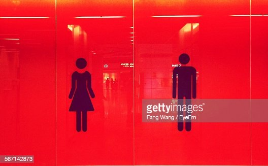 Male And Female Restroom Sign On Red Wall