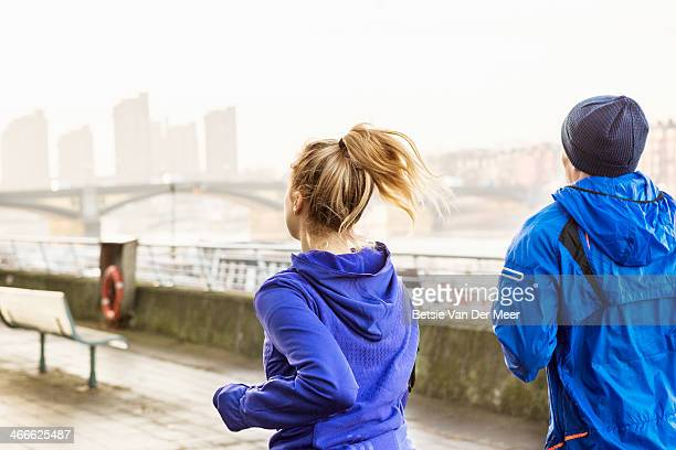 male and female runners running in city.