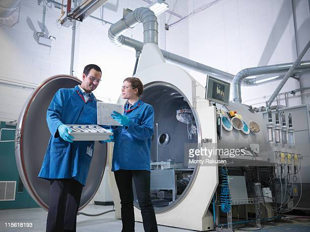 Male and female scientist with product, stood in front of vacuum tank in engineering factory