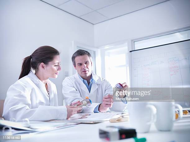 Male and female scientists in office discuss product prototypes they are holding.