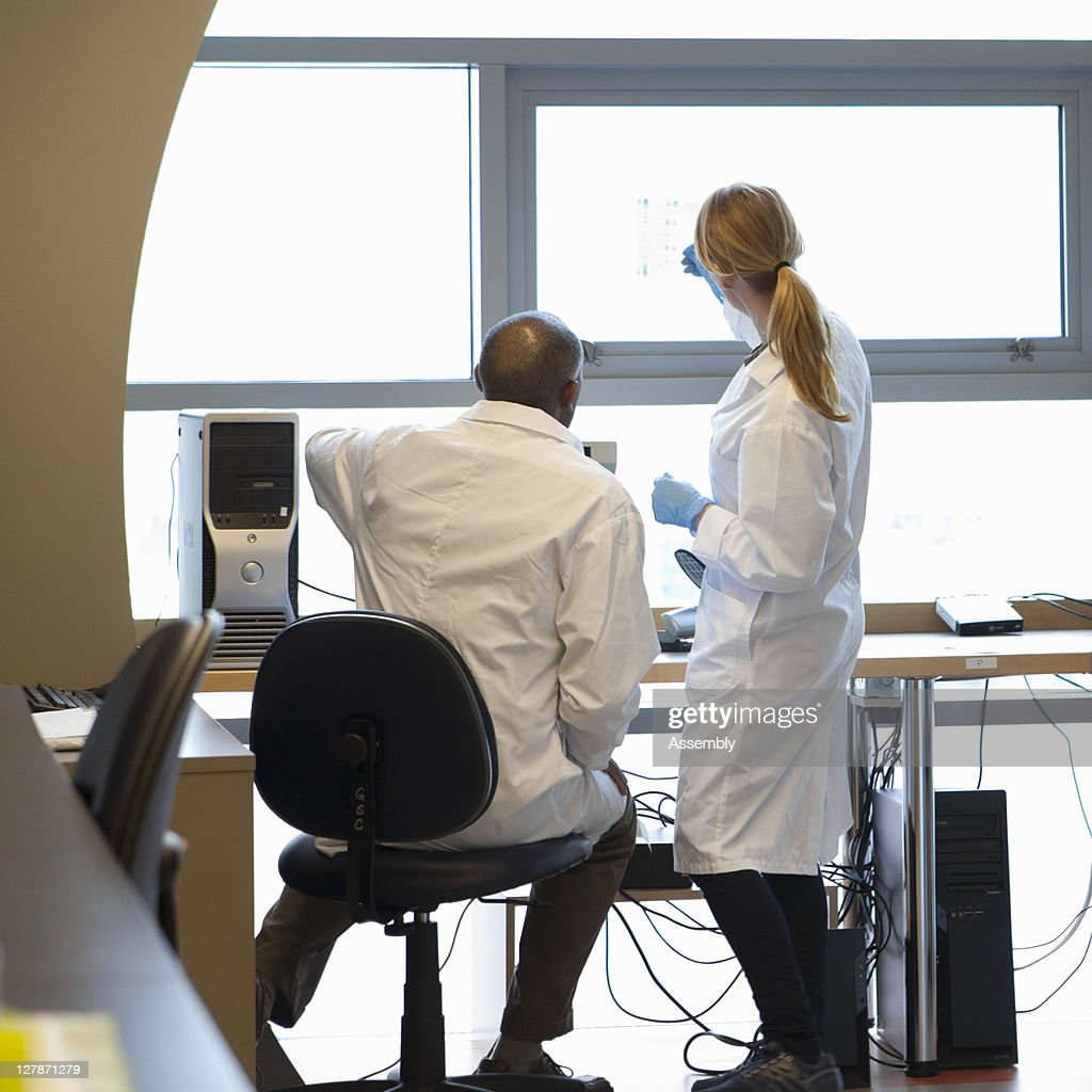 Male and female scientists look at a DNA gel : Stock Photo