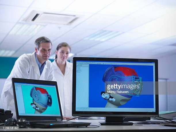Male and female scientists look at on-screen CAD drawings of product prototypes in laboratory
