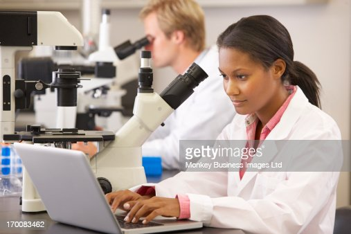 Male And Female Scientists Using Microscopes In Laboratory : Stock Photo
