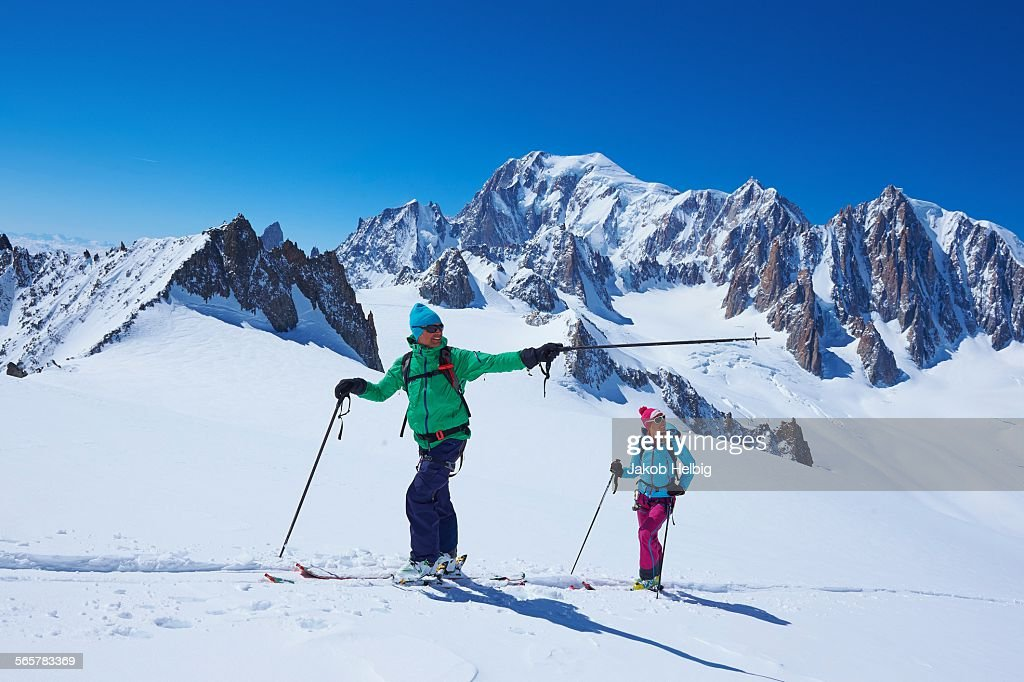 Male and female skiers pointing from Mont Blanc massif, Graian Alps, France
