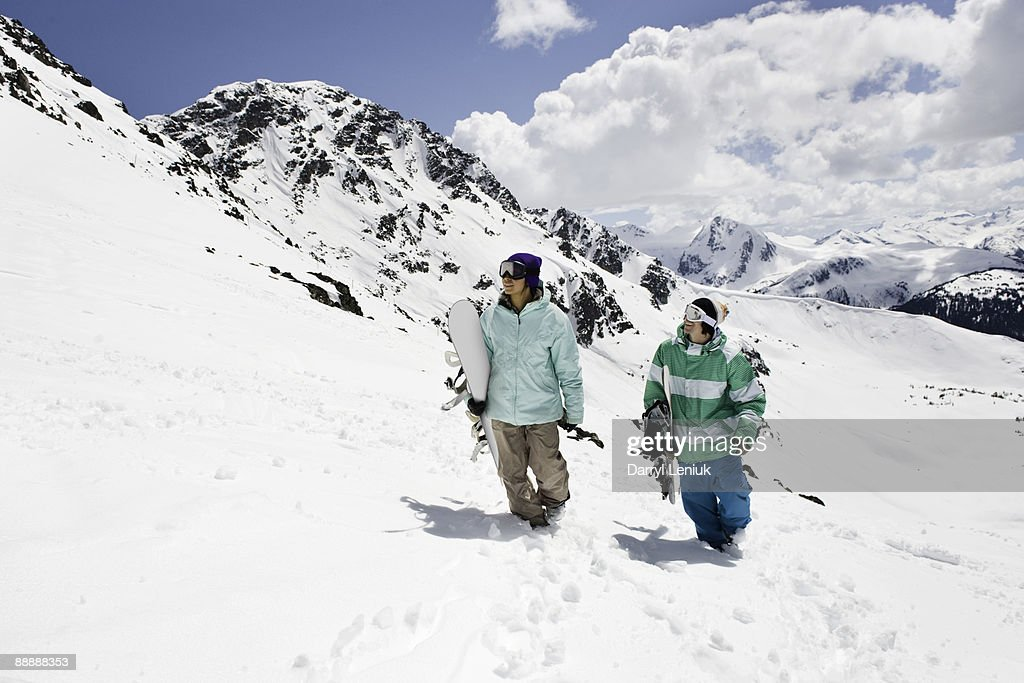 male and female snowboarders carrying boards uphil : Stock Photo