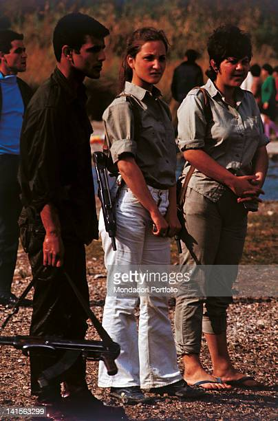 Male and female soldiers armed with Uzi machine guns are guarding the Dead Sea coast in a bathing establishment Ein Feshkha 1971