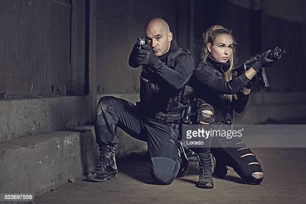 Male and Female swat team members posing in urban setting