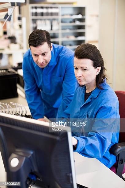 Male and female technicians using computer together at desk in industry