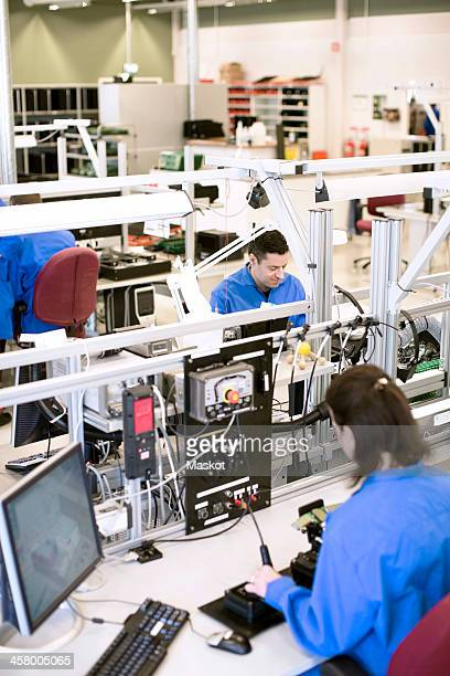 Male and female technicians working in electronics industry