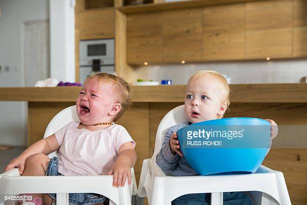 Male and female twin toddlers in high chairs