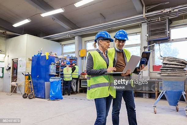 Male and female workers using laptops in factory