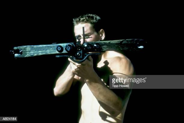 Male archer aiming crossbow, close up, portrait
