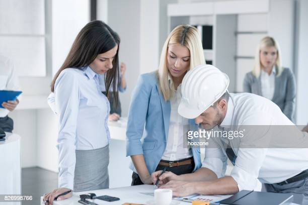 Male architect explaining plans to two young women