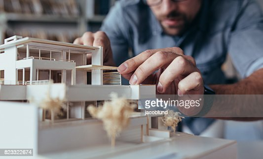 Male architect hands making model house : Stock Photo