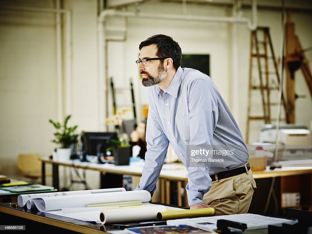Male architect leaning on table in office